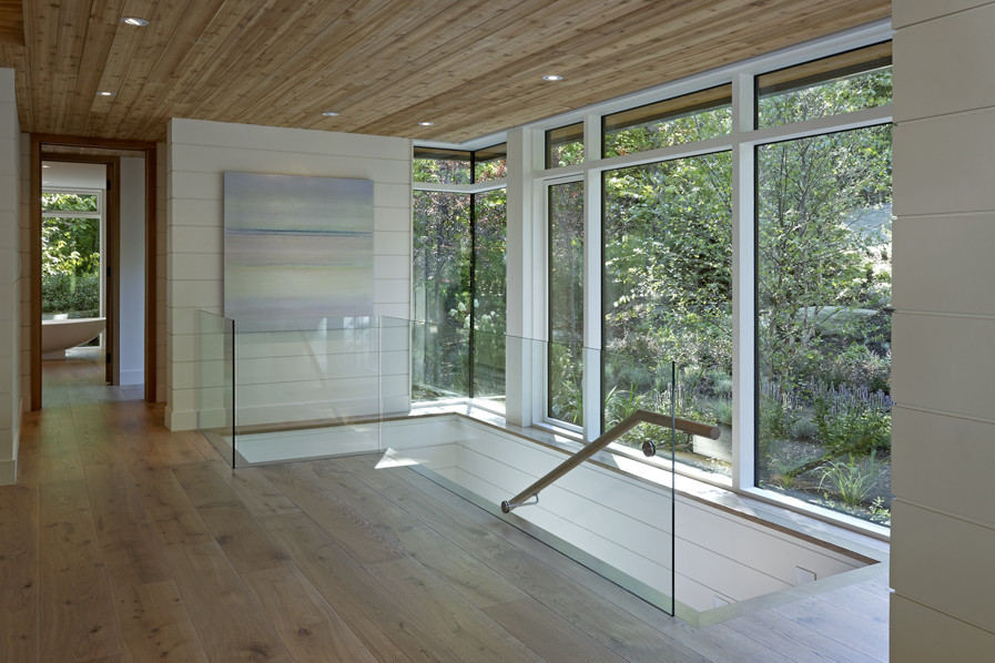 Front entrance with wood ceiling and staircase to lower level with glass partition and glazed wall with view of trees