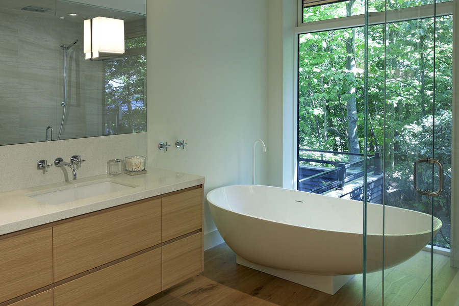 Bathroom with wood vanity, glass shower, and free standing white soaker tub and glazed feature wall with views of trees