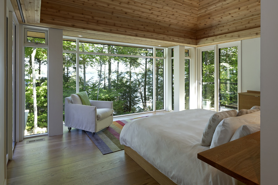 Bedroom with wood tiered ceiling and glazed walls with views of trees and lake