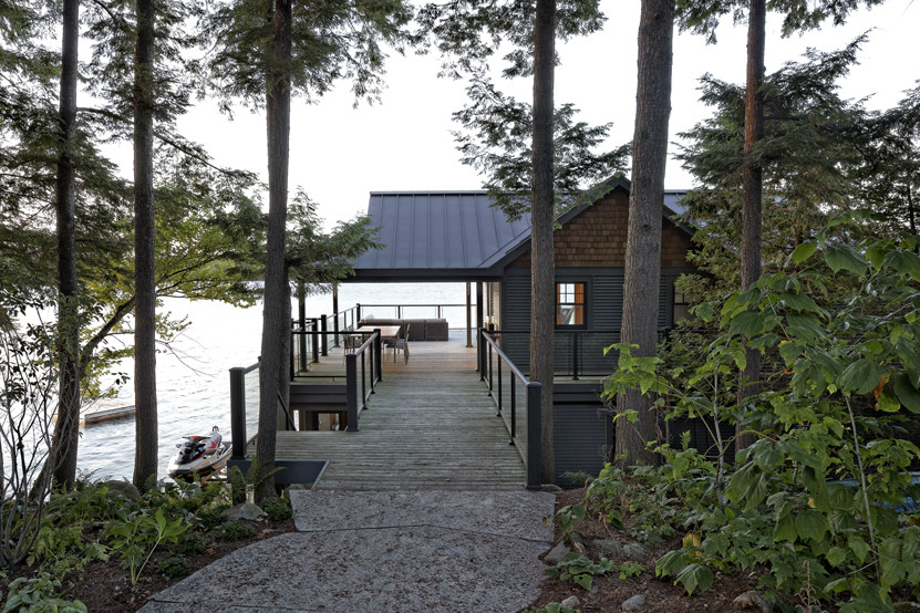View through trees of stone walkway to boathouse with views of lake