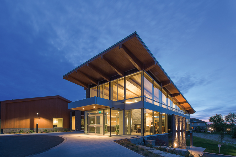 Front entrance to illuminated two-storey building with glass facade and wood cantilever roof at dusk