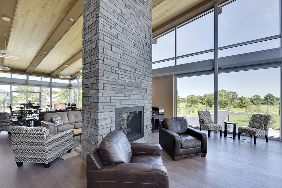 Common area lounge with double height stone fireplace, lounge and dining seating, wood ceiling, glazed walls and clerestory windows
