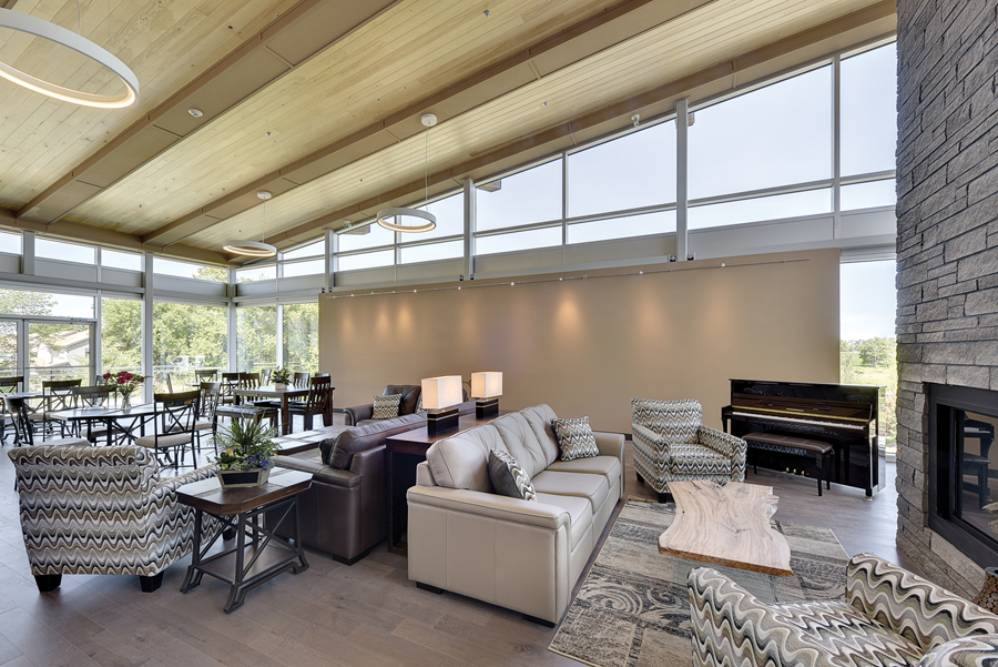 Common area lounge with double height stone fireplace feature, lounge and dining seating, piano, wood ceiling and large clerestory windows