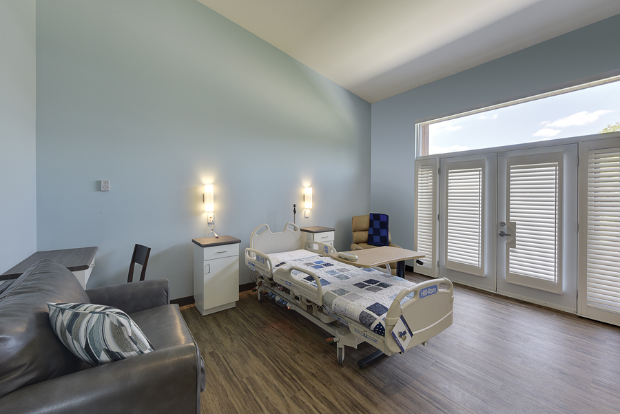 Hospice room with hospital bed, overstuffed chair, light blue walls and white double doors leading outside with clerestory windows above