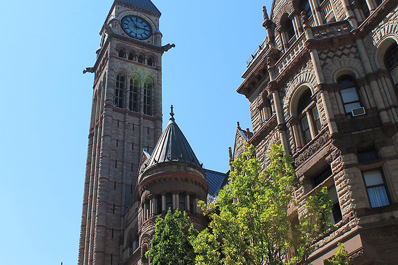 View looking up at front façade with bell tower and green trees in foreground
