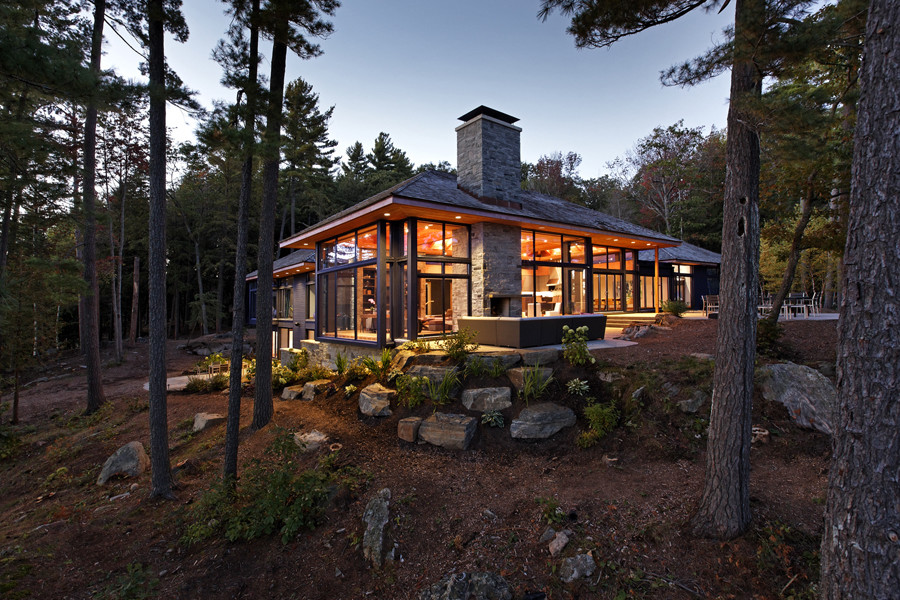 Illuminated cottage at dusk with glazed walls throughout with trees and rocks in foreground