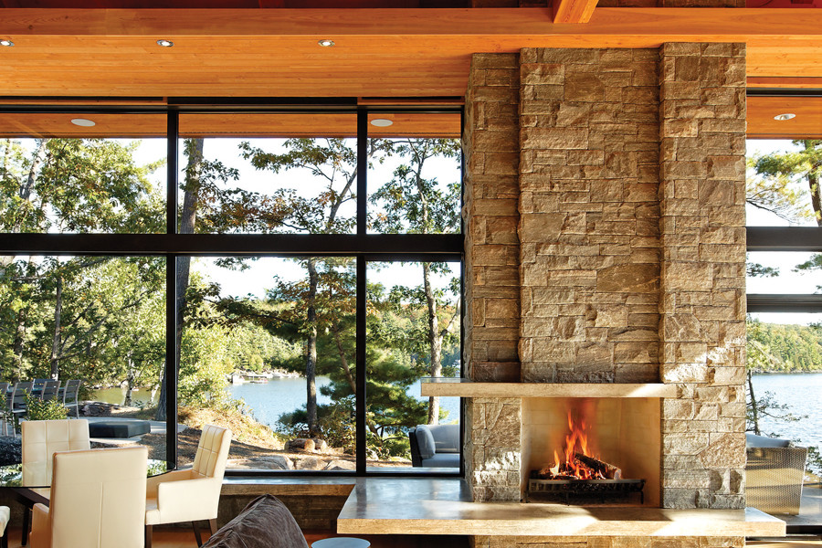 Floor to ceiling stone fire place in living room with views of trees and lake through glazed walls
