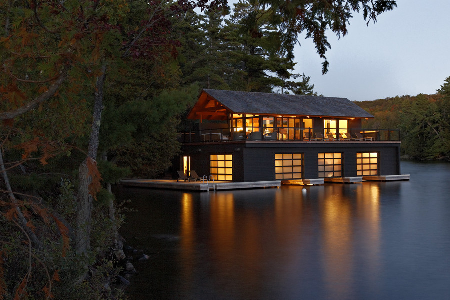 View from lake at dusk of illuminated three-slip boathouse with second storey living space nestled in trees