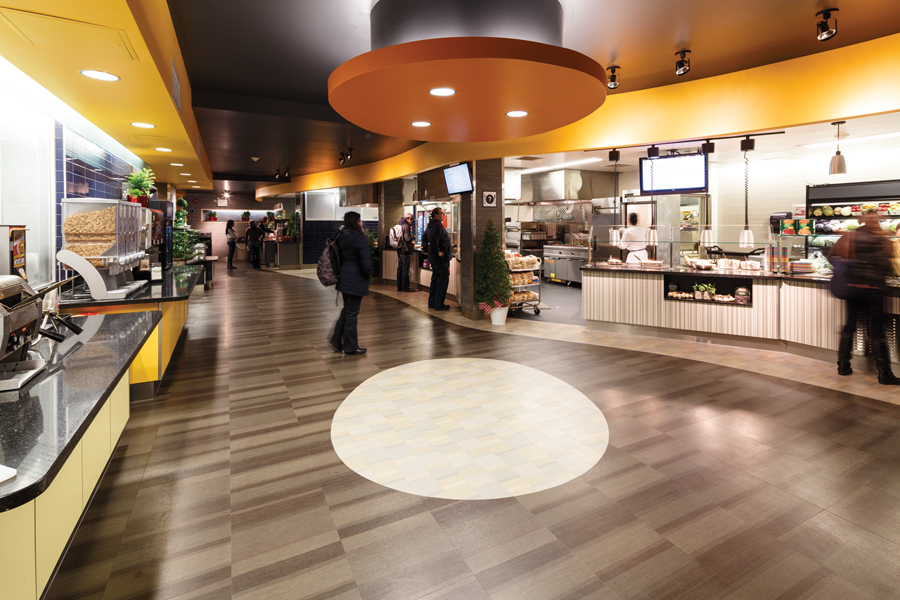 Students browsing food market stalls on right and self serve cereal bar on left with yellow counter and ceiling feature