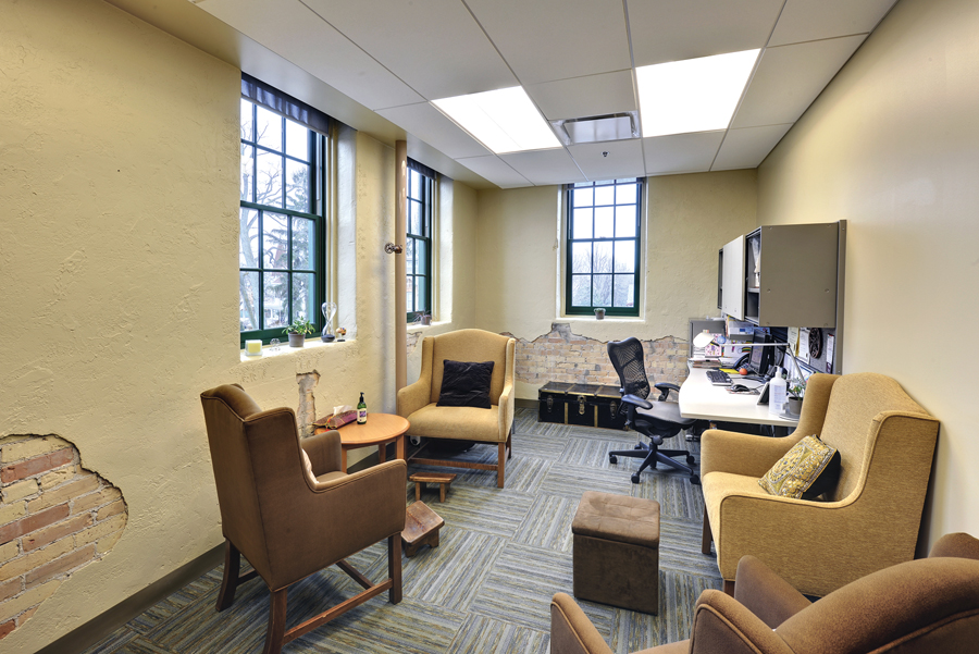 Yellow doctor's office with exposed brick wall features, three large leaded glass windows, desk and guest seating