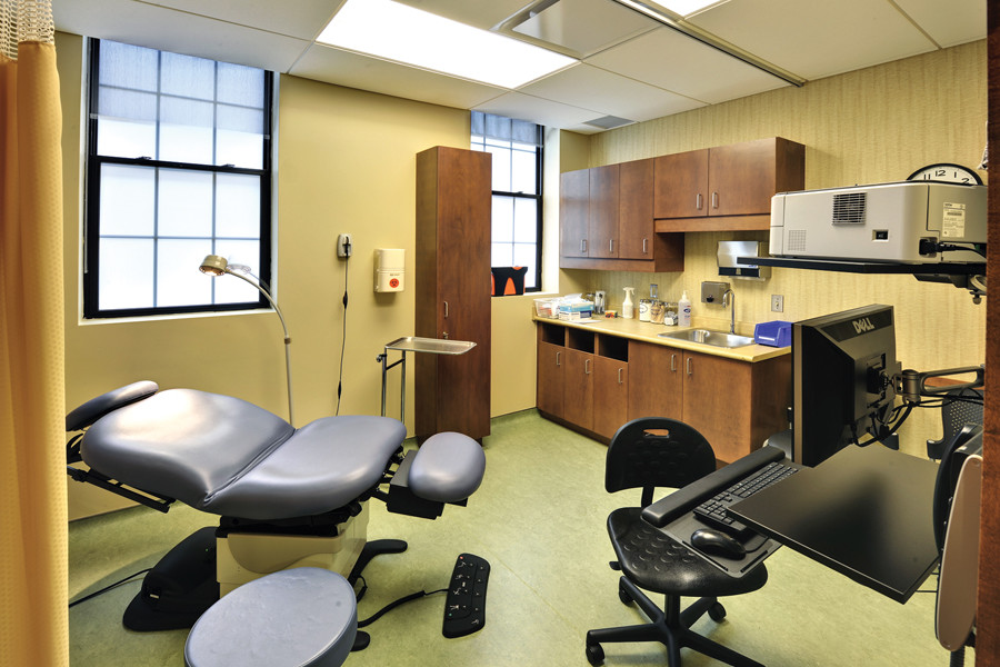 Yellow exam room with two large leaded glass windows, patient chair, and desk, computer and supply cupboard for doctor