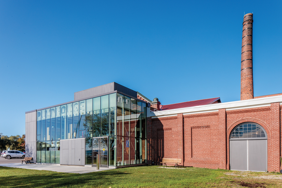 Double height glazed addition to original red brick museum with Pumphouse lettering on glass and smoke stack in background