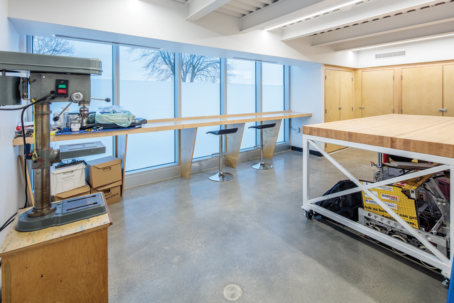 Machine shop area with island work space and large windows with stool seating and millwork storage cupboards