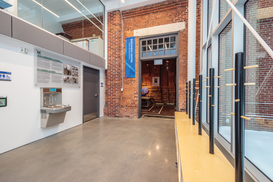 Double height front entrance lobby featuring connection point of glass addition and original red brick wall and glazed second storey corridor