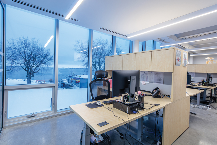 Modular office work stations with glazed wall in background with views of trees