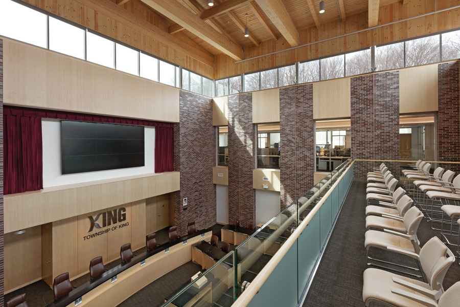 Double height council chamber with upper level gallery seating, brick and wood materiality, wood rafter ceiling and clerestory windows