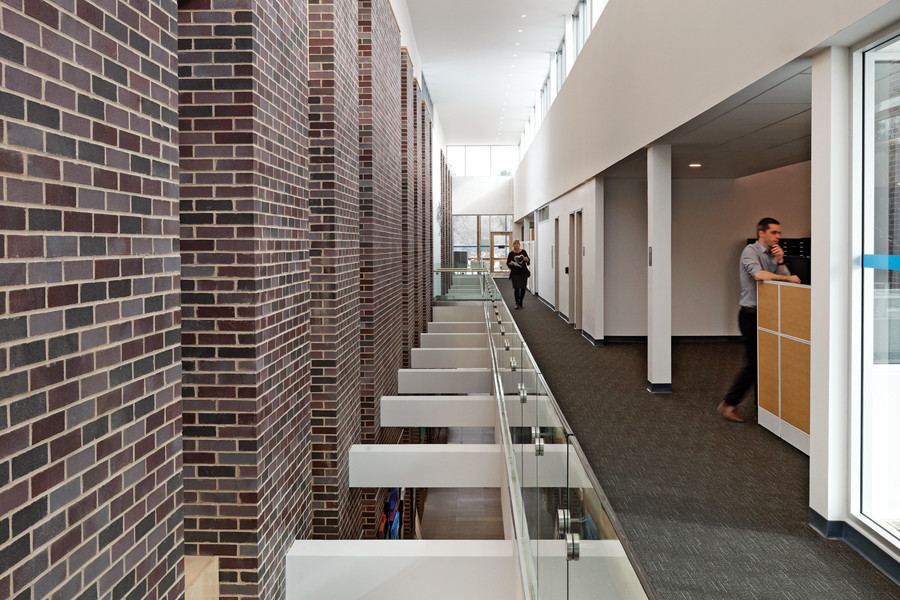 Open concept second storey corridor with views down to first level, glass guard rail and double height brick wall on left and offices on right