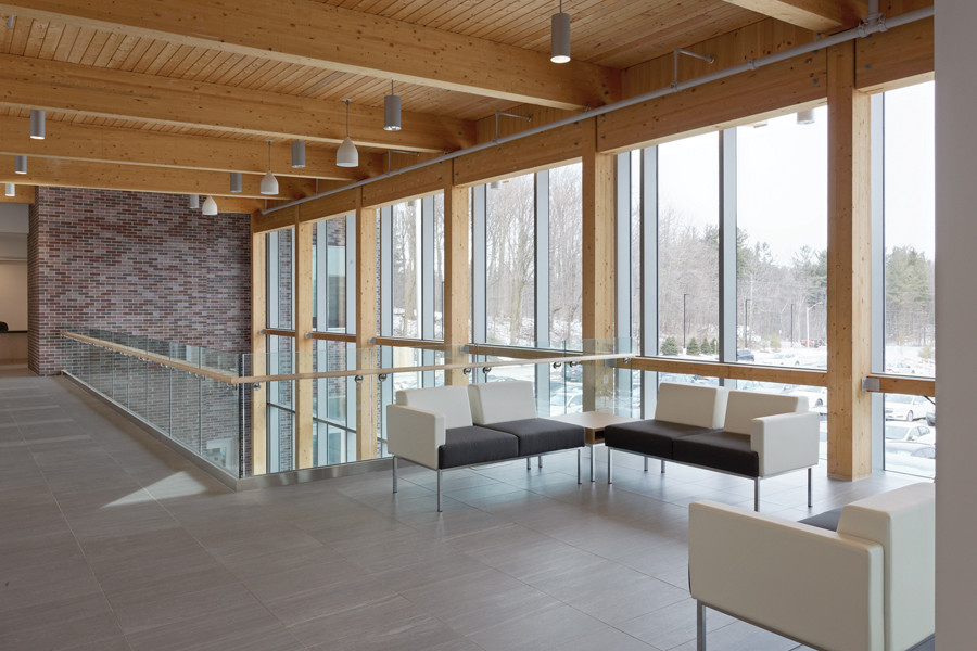 Upper level lounge area beside staircase with glass guard rail and slanted wood rafter ceiling with double height glazed wall