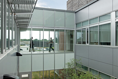 View of transparent first floor and second floor glazed corridors from interior courtyard with trees