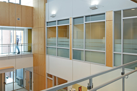 Glazed second storey corridor overlooking double height front entrance atrium with white pendant lighting