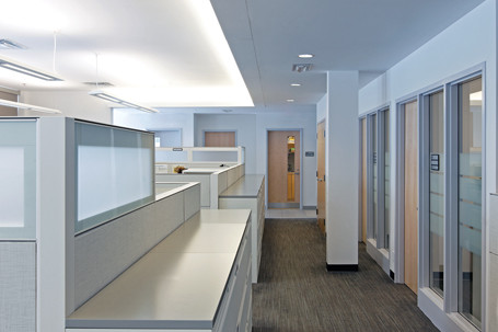 White corridor with partitioned workstations on left and glazed meeting rooms on right