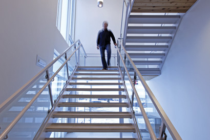 Man on open wood staircase with glass partition, wood ceiling and white pendant lightings