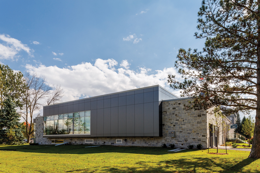 View of addition with large windows intersecting original stone façade from grassy lawn with trees on a sunny day
