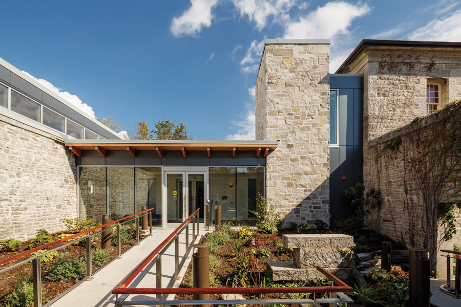 Ramp from courtyard garden to glazed front entrance with wood cantilever roof and stone façade with clerestory windows on left