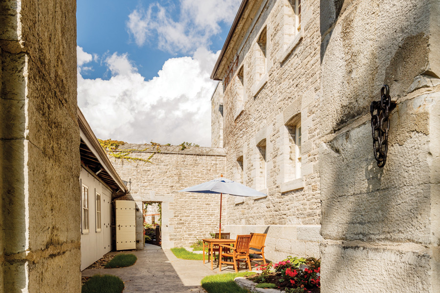 View of interior stone walled courtyard garden with lounge seating from archway with blue skies