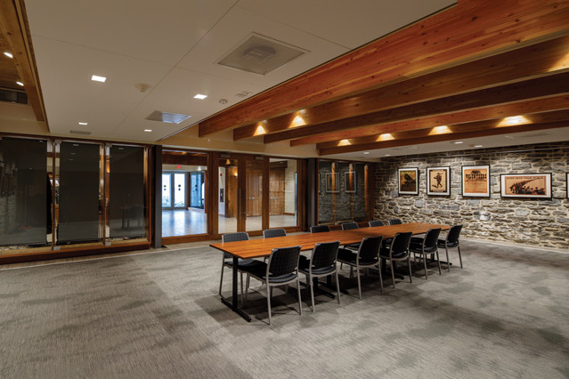 Glazed meeting room off front entrance lobby with stone walls with hung pictures and dropped wood rafter ceiling