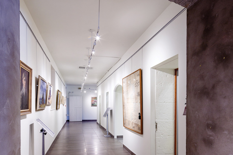 White walled gallery corridor with dropped track lighting from stone archway