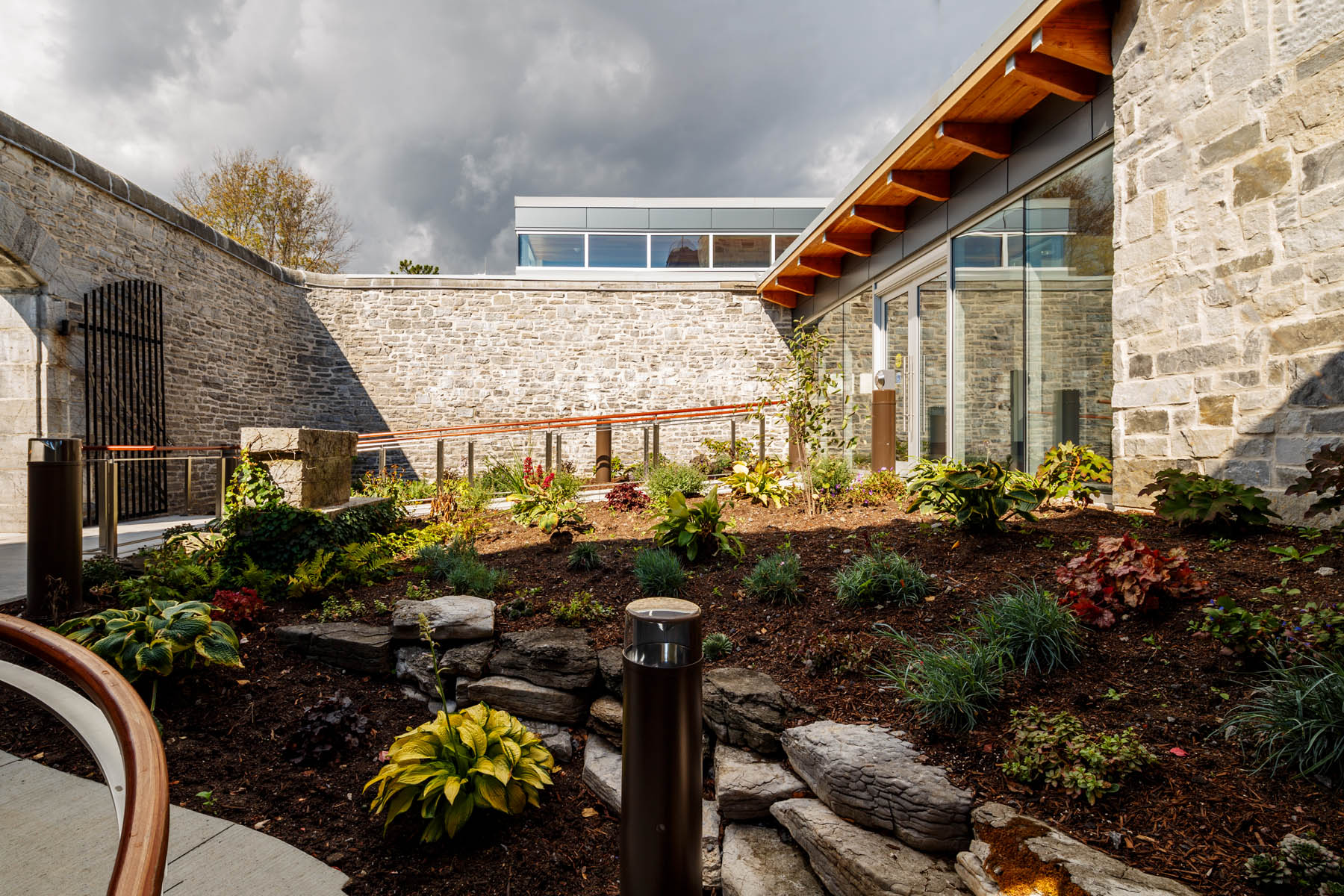 Stone walled garden and glazed entrance with wood cantilever roof, and clerestory windows of addition and stormy skies in background