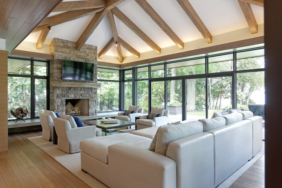 Living room with seating, stone fire place, exposed rafter ceiling and glazed walls on all sides with views of lake and trees