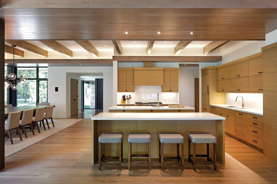 Open concept kitchen and dining room with millwork island and cupboards and exposed rafter ceiling