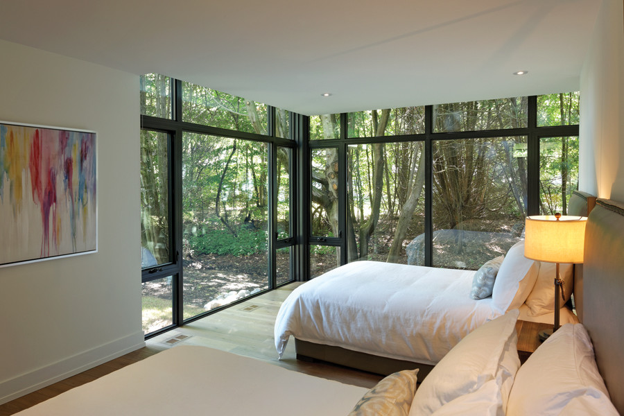 Bedroom with glazed walls and views of trees
