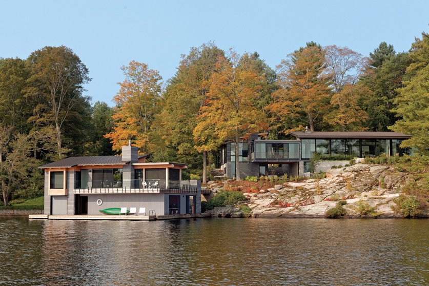 Day view of cottage and boathouse with trees and rockface from south end of Lake Joseph, Muskoka