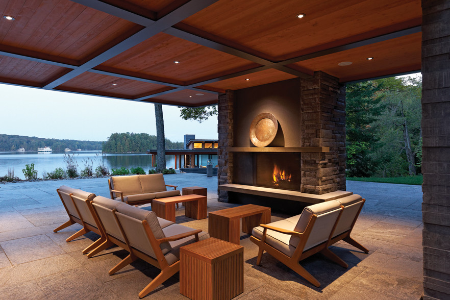 Dusk view of illuminated covered porch with seating and fireplace and views through to boathouse and Lake Joseph
