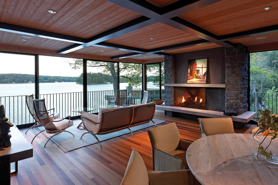 Screened porch with seating and fireplace overlooking south end of Lake Joseph, Muskoka