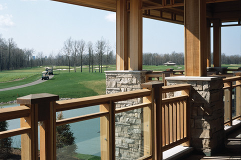 View of golf course from second storey patio with wood framed glass partitions and wood cantilever roof