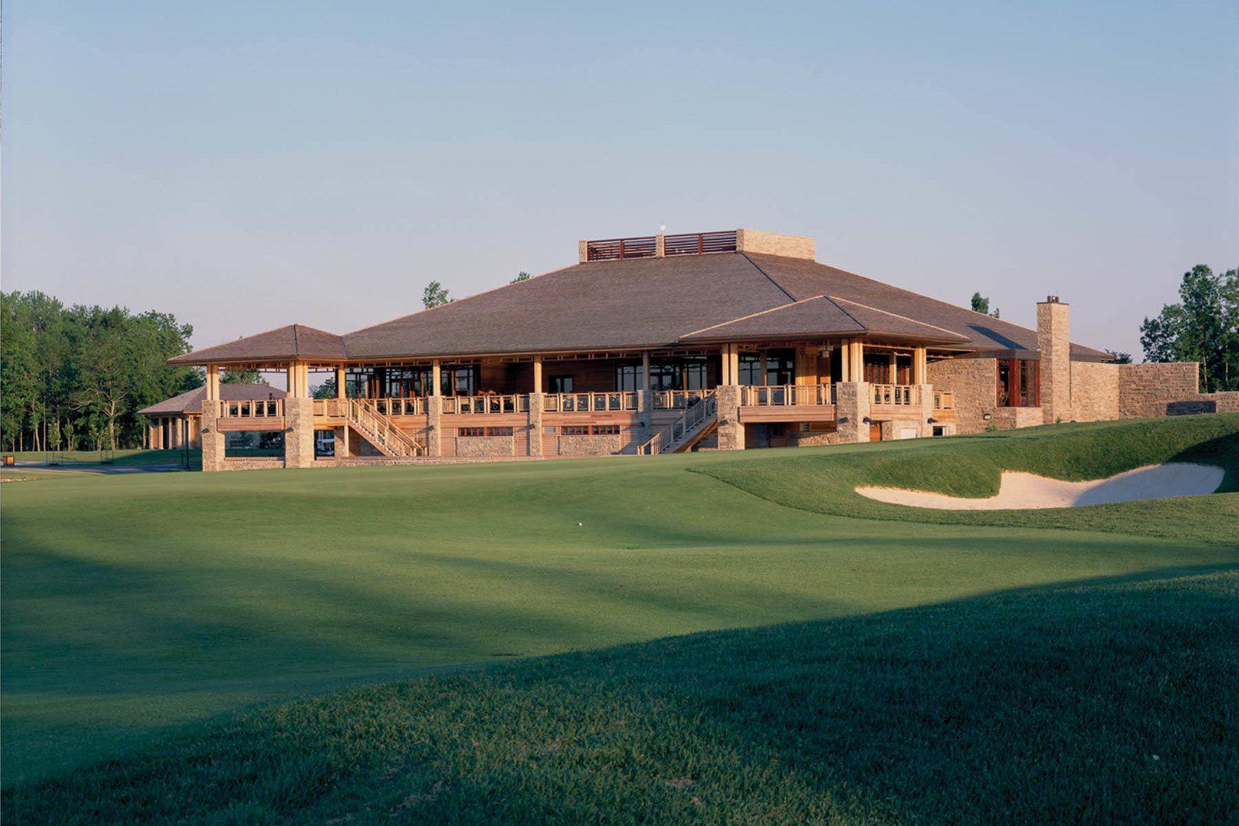 Clubhouse with golf course in foreground and trees in background