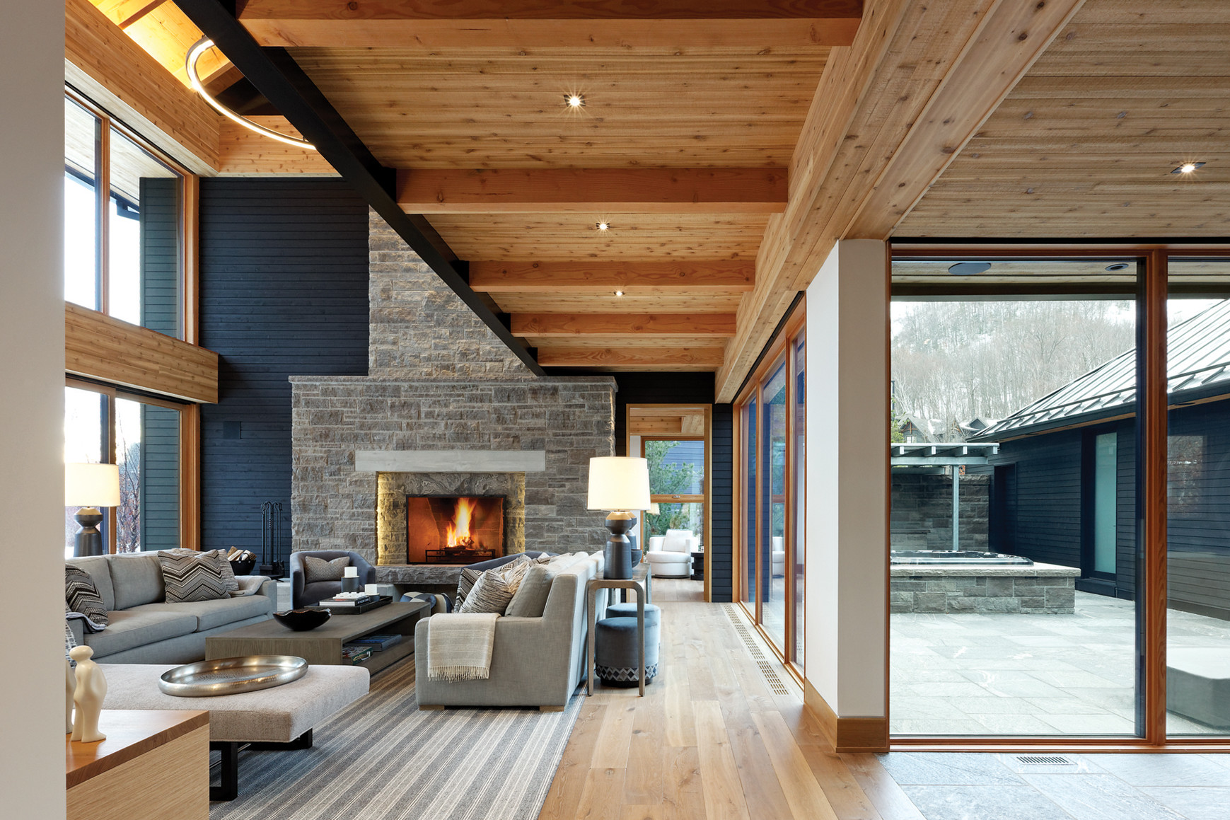 Living room with stone fireplace and couch seating overlooking glazed interior courtyard with hot tub on the right