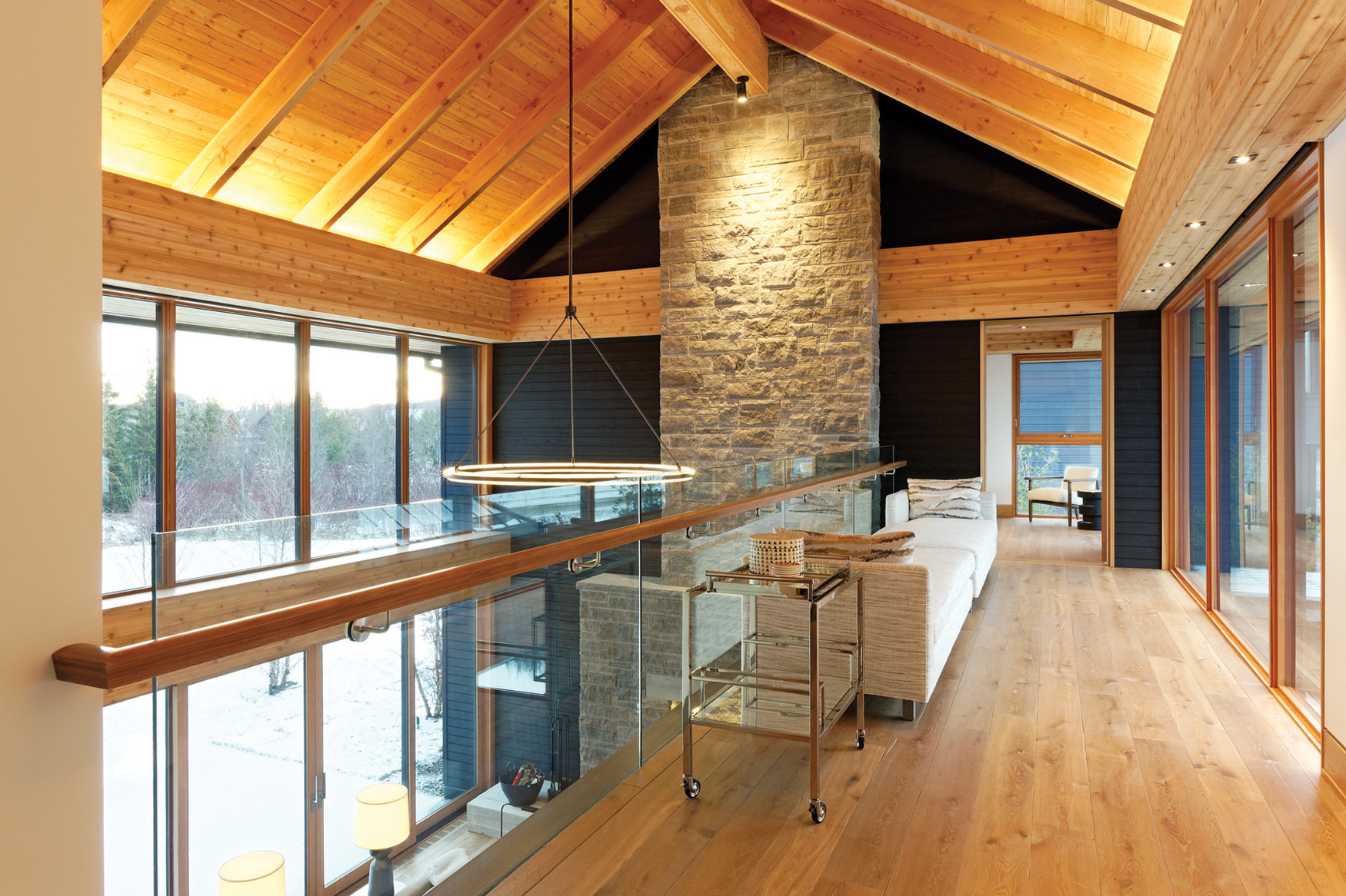 Second storey hallway overlooking living room through to landscape with double height stone fireplace and wood rafter ceiling