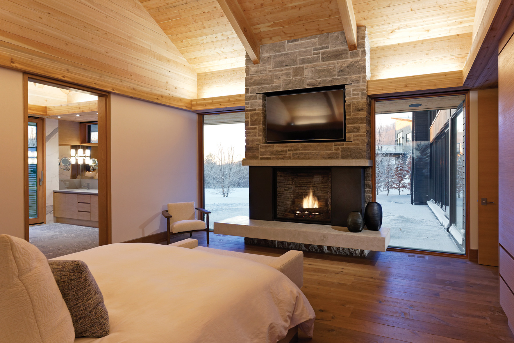 Bedroom with stone fireplace with floor to ceiling glass windows