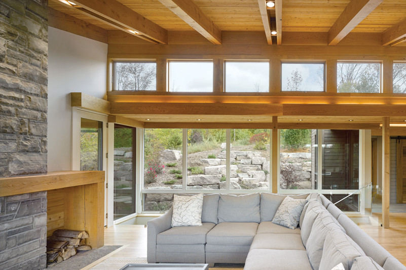 Living room with sectional seating with views through floor to ceiling and clerestory windows of rockface and greenery outside