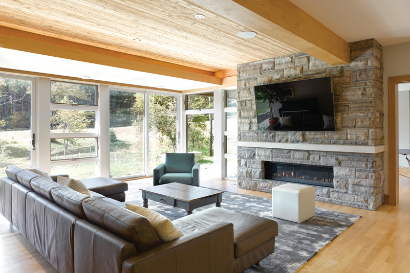 Living Room with stone fireplace and sectional seating with views through glass doors and windows to greenery outside on the left