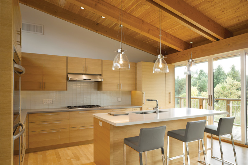 Kitchen with wooden ceiling rafters, cupboards, and island with bar stools and view through glass doors to greenery outside on the right