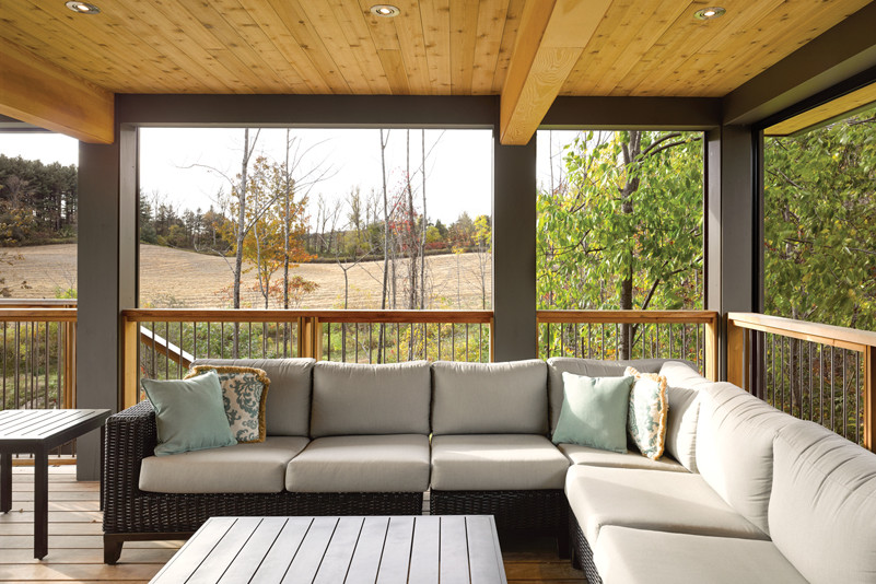Covered porch with sectional wicker seating with views to country side