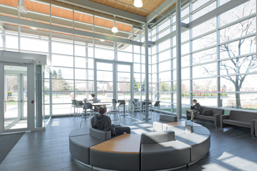Modular student lounge seating in glazed double height front entrance lobby with steel window framing and wood slat ceiling