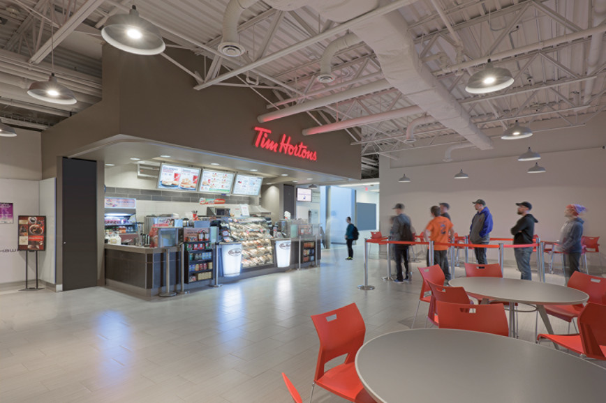 Students lined up at Tim Hortons inside white corridor, with informal student seating and exposed beam ceiling