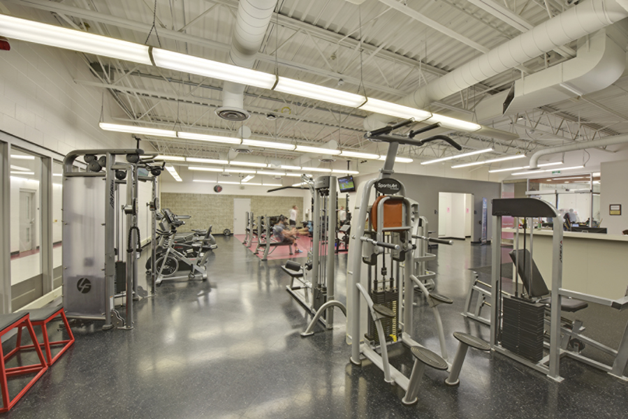 White fitness room with exercise equipment, dropped fluorescent lighting and exposed beam ceiling